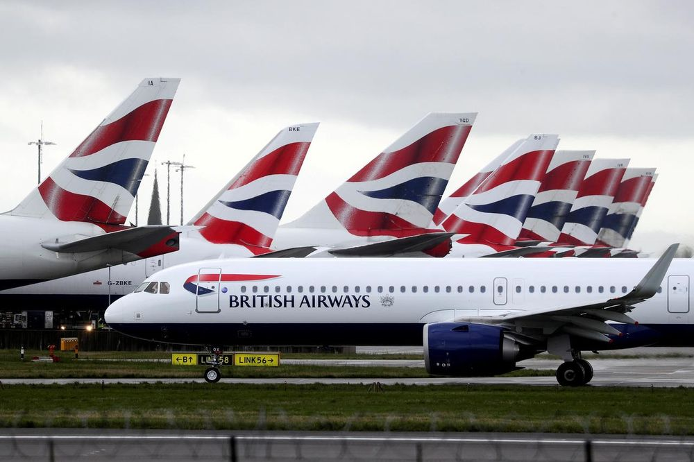 A British Airways plane taxis past tail fins of parked aircraft to the runway near Terminal 5 at Heathrow Airport in London, Britain March 14, 2020. — Reuters pic