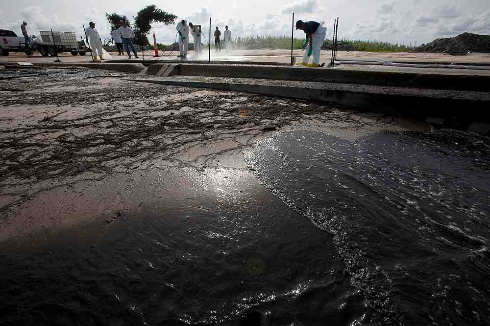 Workers pressure-wash oil from the Deepwater Horizon spill from a roadway in Waveland, Mississippi, July 7, 2010. — Reuters pic