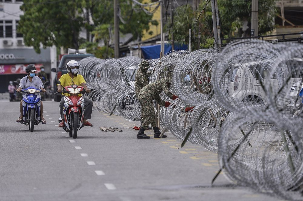 Armed Forces personnel erect barbed wire fencing in Selayang Baru amid the enhanced movement control order April 26, 2020. ― Picture by Mera Zulyana