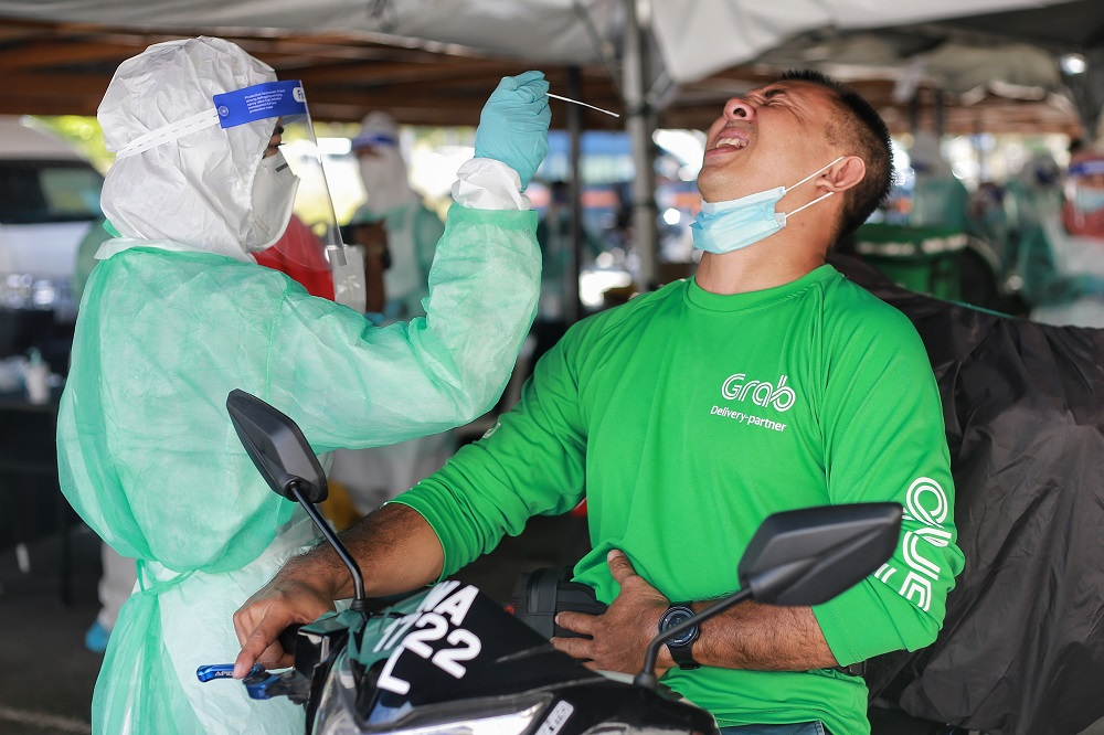 A health worker collects a coronavirus test sample from a food delivery rider at the Gombak Land and District office April 22, 2020. ― Picture by Ahmad Zamzahuri