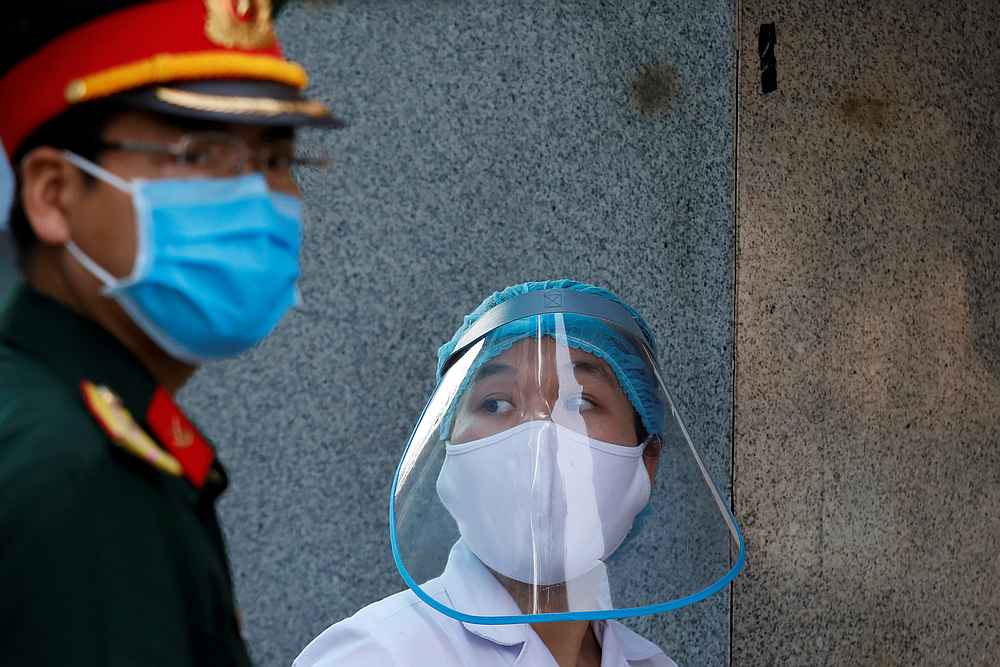 A health worker wears a protective face shield next to a soldier at the quarantined Nephrology hospital during the Covid-19 outbreak in Hanoi, Vietnam April 14, 2020. — Reuters pic