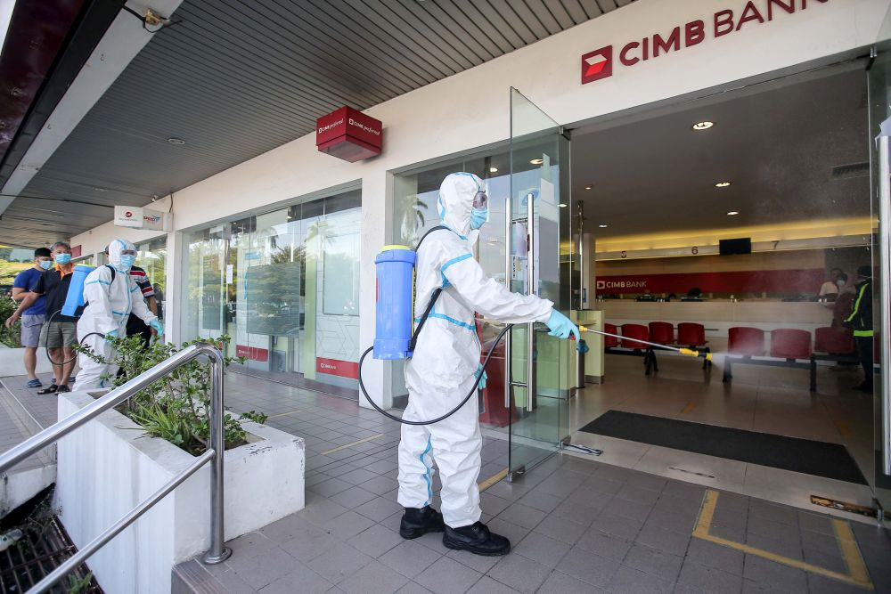 A city council worker sprays disinfectant at a CIMB Bank branch in Ipoh April 6, 2020. CIMB said five staff from CIMB Mobile Sales Force (MSF), Kota Damansara who have been in close proximity with a confirmed Covid-19 patient are now in Sungai Buloh Hospital for Covid-19 testing and are undergoing quarantine. — Picture by Farhan Najib
