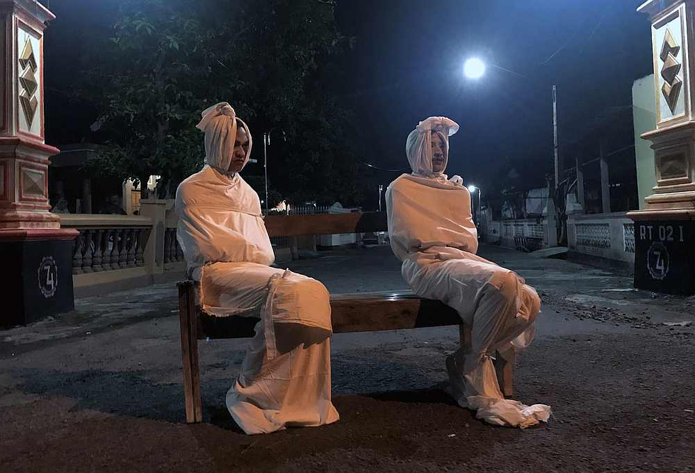 Volunteers Deri Setyawan, 25, and Septian Febriyanto, 26, sit on a bench as they play the role of 'pocong,' or known as 'shroud ghost,' to make people stay at home in Kepuh village, Central Java, Indonesia, April 1, 2020. — Reuters pic