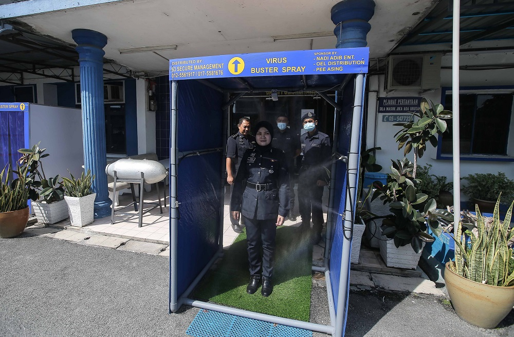 A police personnel tests a disinfection chamber at the entrance of the Kampung Tawas police station in Ipoh April 14, 2020. ― Picture by Farhan Najib