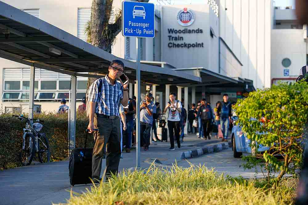 Malaysians returning home from Singapore on March 17, 2020. A number of Malaysians have remained in Singapore, but some have found themselves out of work. — TODAY pic