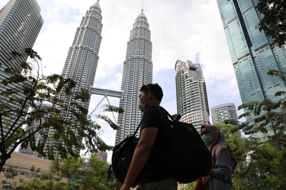 Tourists wearing masks pass by Petronas Twin Towers in Kuala Lumpur, Malaysia, January 31, 2020. —Reuters pic