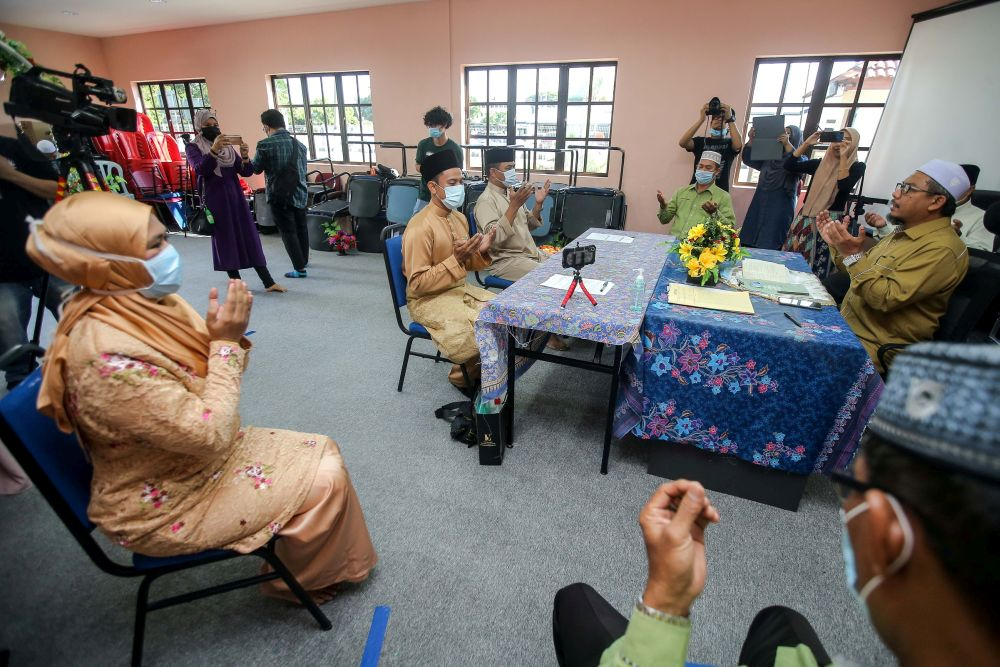 A couple observe social distancing guidelines while performing their 'nikah' vows at the Ipoh District Islamic Religious Office April 22, 2020. — Picture by Farhan Najib
