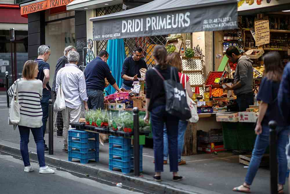 People queue in front of a fruit and vegetables shop at Rue des Martyrs, as the spread of Covid-19 continues in Paris, France April 18, 2020. — Reuters pic
