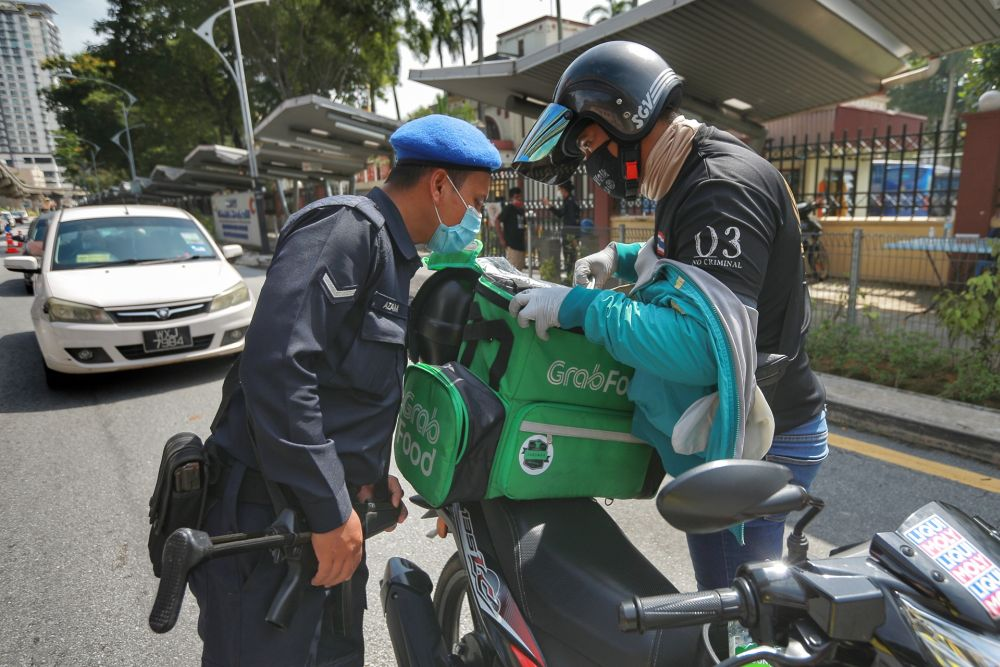 A police personnel conducts checks on a food delivery rider during a road block in Kuala Lumpur April 7, 2020. — Picture by Ahmad Zamzahuri