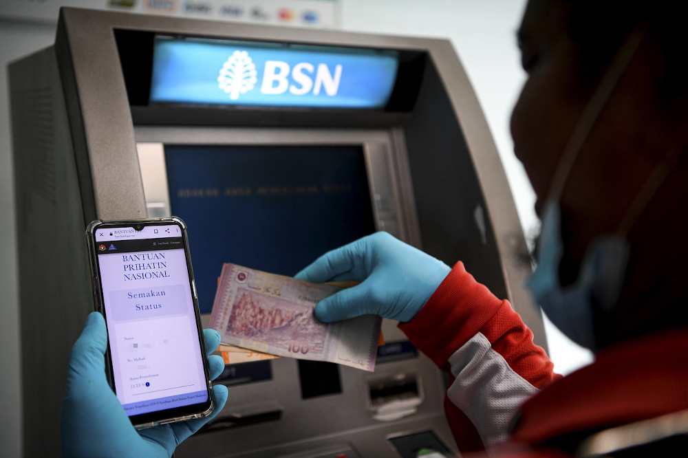 A man withdraws money from the ATM after receiving approval for the Prihatin aid package in Kuala Lumpur April 6, 2020. A total of 1.93 million people in Sabah and Sarawak have received the Bantuan Prihatin Nasional, amounting to RM2.1 billion. — Bernama pic
