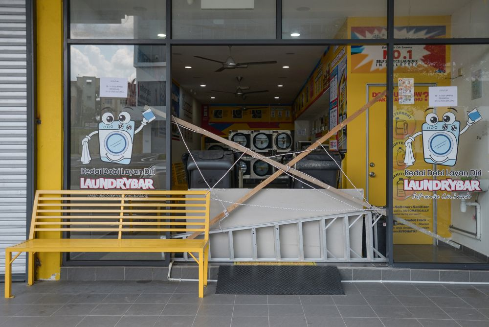 A self-service laundrette in Shah Alam is cordoned off from the public as the movement control order enters phase three on April 15, 2020. — Picture by Miera Zulyana