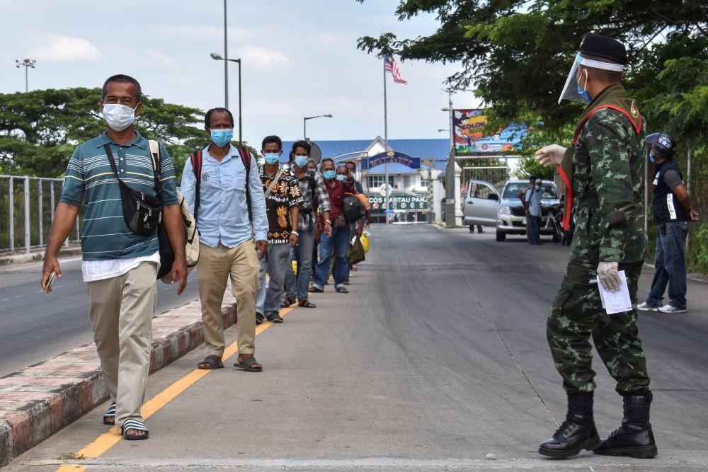 Thai people wearing face masks walk in line at the Thai-Malaysia border Sungai Kolok district, Narathiwat April 18, 2020. — Reuters pic