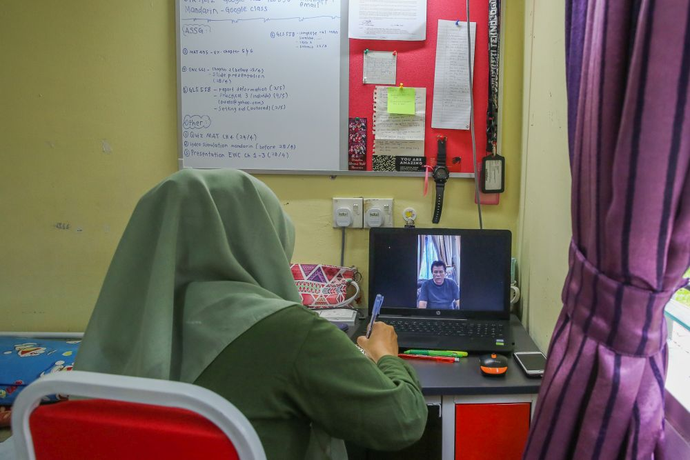 A Universiti Teknologi Mara student takes online lessons in her dormitory room during the third phase of the movement control order in Shah Alam April 22, 2020. — Picture by Yusof Mat Isa