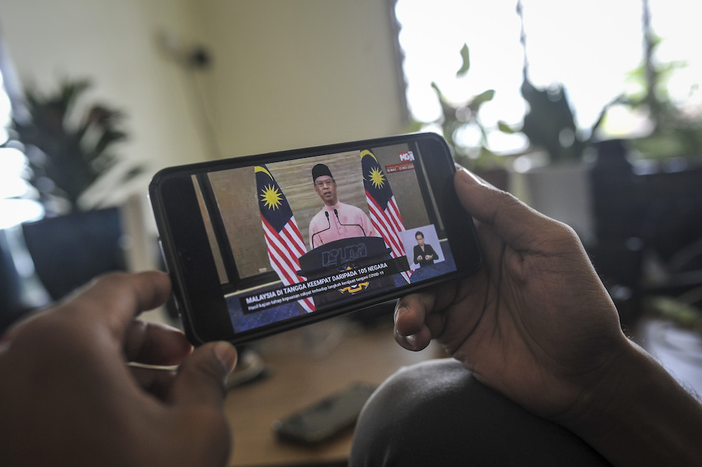 A man watches a live telecast of Prime Minister Tan Sri Muhyiddin Yassin's special address about the conditional movement control order in Kuala Lumpur May 10, 2020. — Picture Shafwan Zaidon