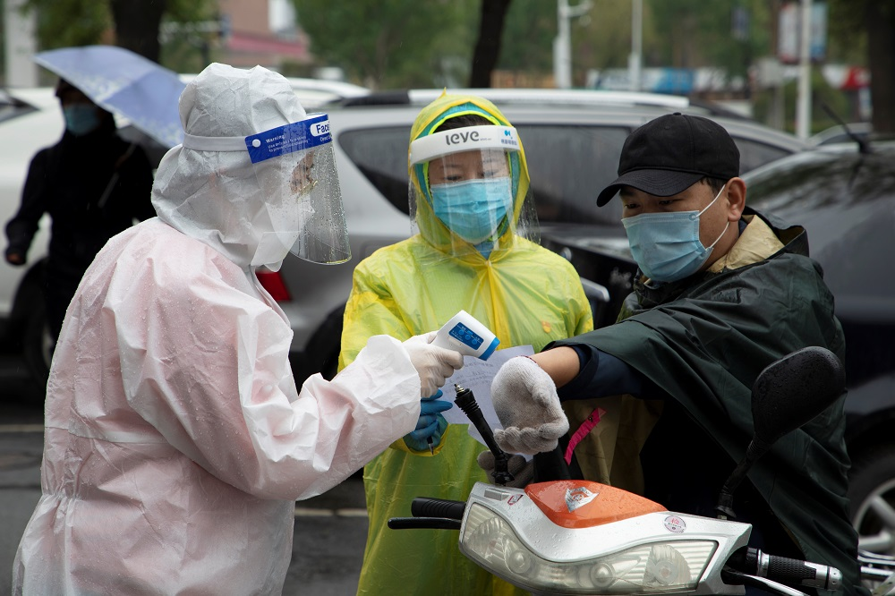 Volunteers in protective gear measure the body temperature of a man at the entrance of a residential compound following the Covid-19 outbreak, in Chuanying district of Jilin, China May 22, 2020. — Picture by China Daily via Reuters