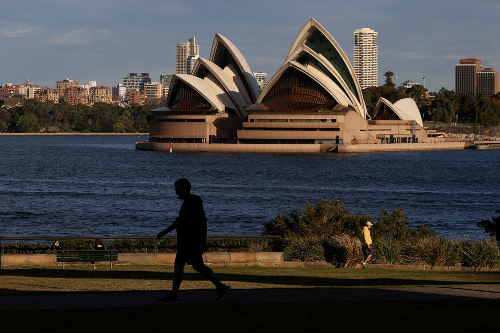 People stroll through a park in front of the Sydney Opera House amidst the easing of the coronavirus disease restrictions in Sydney. Australia has been largely successful in containing the spread of the novel coronavirus, which it attributes to curbs on international travel and tough social-distancing rules. — Reuters pic