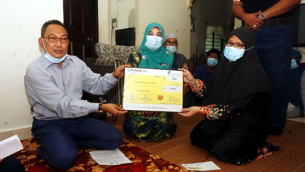 File photo of Deputy Human Resources Minister Awang Hashim presenting a replica of the RM2,000 cheque of SOCSO funeral management benefit and survivor's pension to Nor Hafizah Mohd Aziz in Changlun, May 28, 2020. — Bernama pic