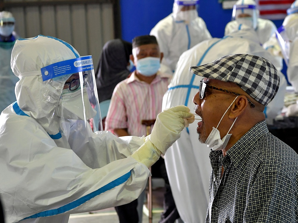 A man undergoes a swab test during a Covid-19 screening exercise at the Datuk Dr Wan Junaidi multipurpose hall in Tabuan Lot, Kuching May 9, 2020. Volunteers aged 60 and above are being sought by MOH to participate in phase three clinical trial of the Covid-19 vaccine. — Bernama pic