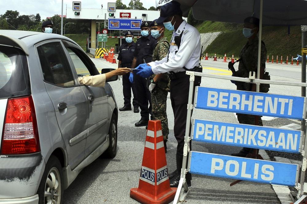 Policemen are seen at a roadblock located at the Seremban Toll Plaza during the first day of Hari Raya Aidilfitri in Seremban May 24, 2020. — Bernama pic