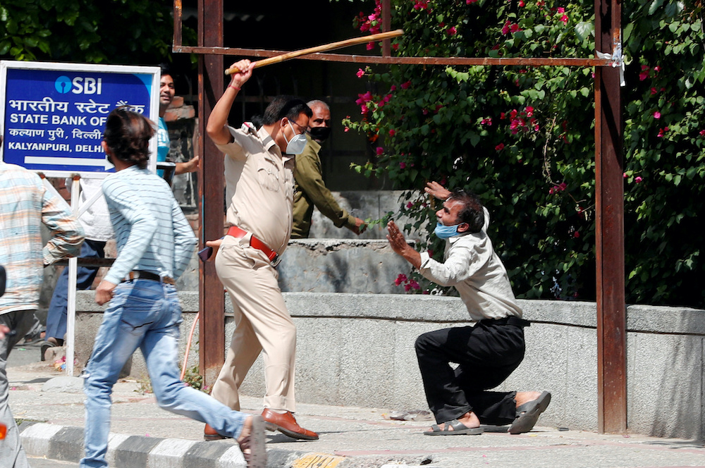 A police officer raises a baton at a man who, according to police, had broken the social distancing rule, outside a wine shop during an extended nationwide lockdown to slow the spread of the coronavirus disease, in New Delhi, India, May 4, 2020. — Reute