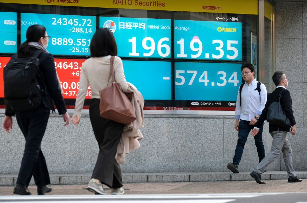Pedestrians walk in front of a quotation board displaying share prices of the Tokyo Stock Exchange in Tokyo. — AFP pic
