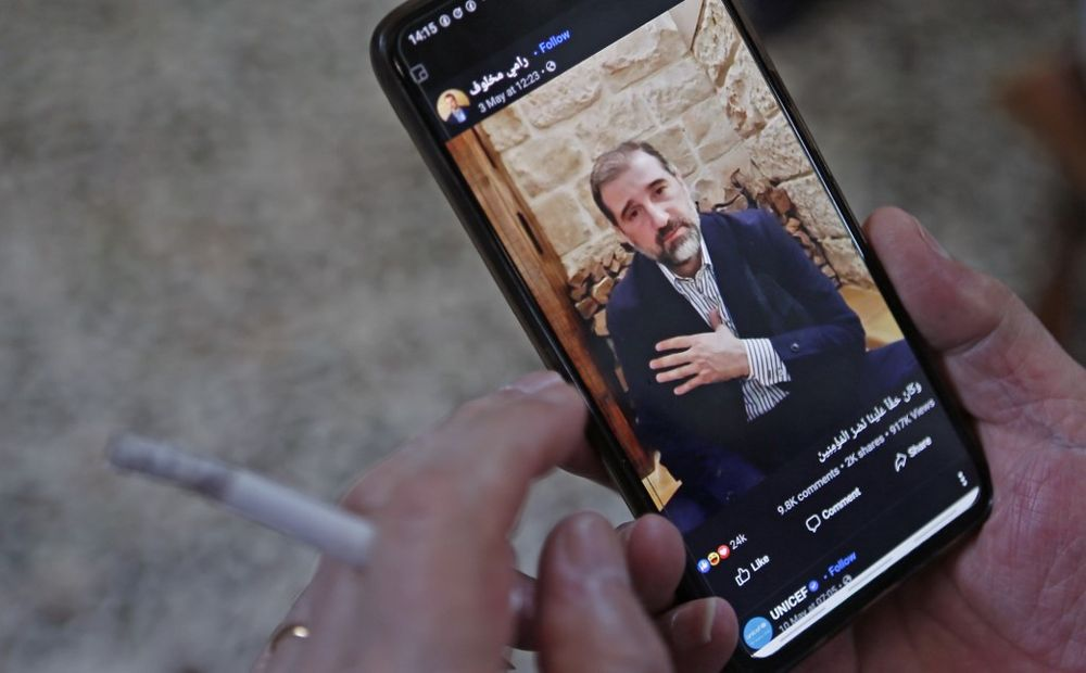 A man watches the Facebook video of Syrian businessman Rami Makhlouf on his mobile in Syria's capital Damascus, May 11, 2020. — AFP pic