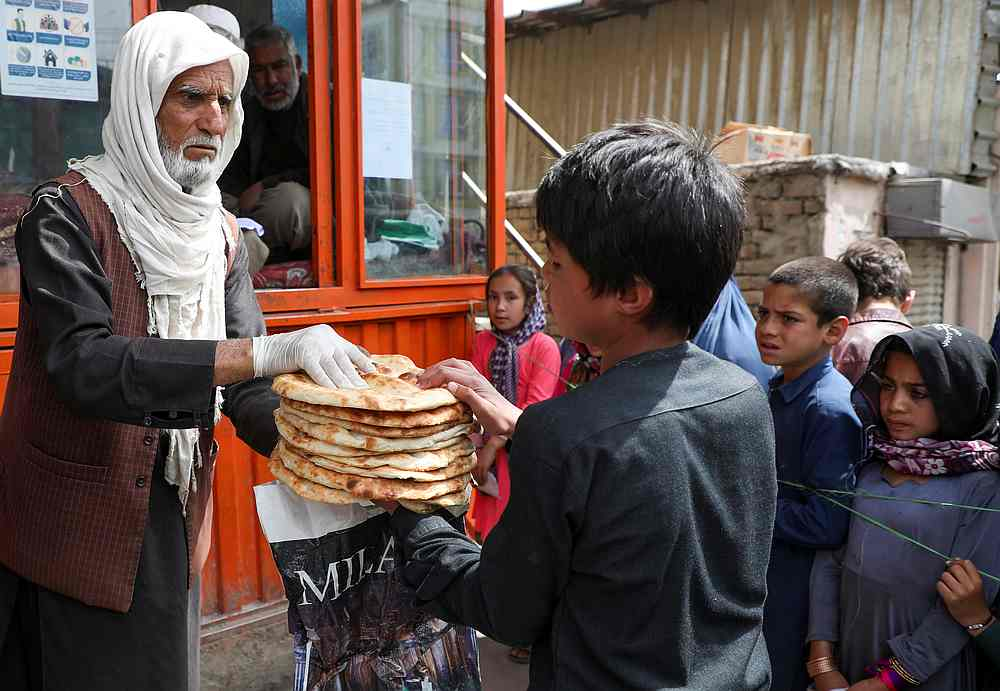 An Afghan boy receives free bread distributed by the government, outside a bakery, during the Covid-19 outbreak in Kabul, Afghanistan May 3, 2020. — Reuters pic