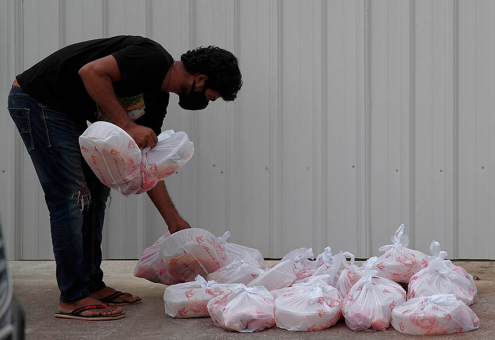 A migrant worker living in a construction site collects meals donated by charities for their Eid-al-Fitr celebrations amid the Covid-19 outbreak in Singapore May 24, 2020. — Reuters pic