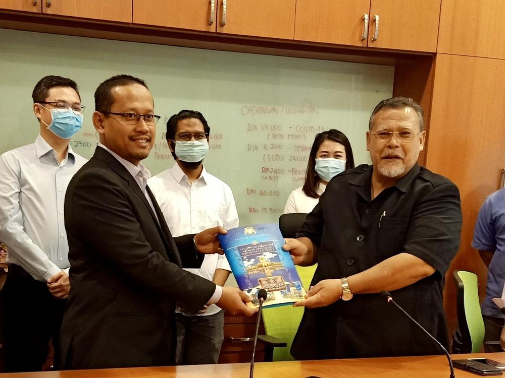 Johor Pakatan Harapan (PH) chief Aminolhuda Hassan (right) handing over the coalition's assemblymen asset declaration to state legislative speaker Suhaizan Kayat in Iskandar Puteri May 31, 2020. — Picture by Ben Tan