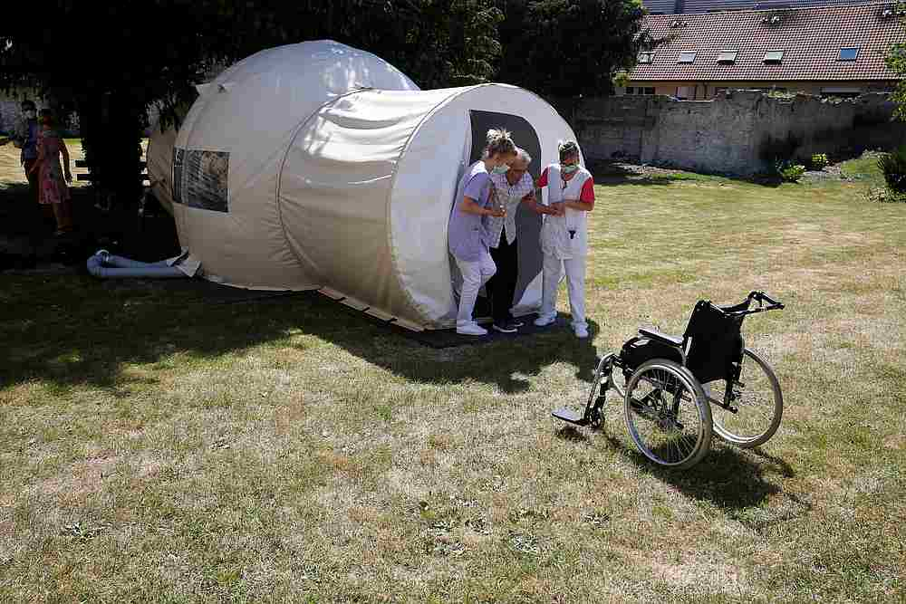 Nurses help a resident to leave a bubble room for visits between residents and their families installed in the garden of the Fondation Shadet Vercoustre retirement home in Bourbourg, France, May 25, 2020. — Reuters pic