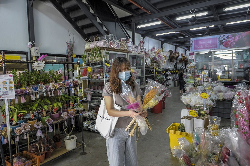A woman is seen choosing stalks of flowers at a florist in Kuala Lumpur May 4, 2020. ― Picture by Shafwan Zaidon