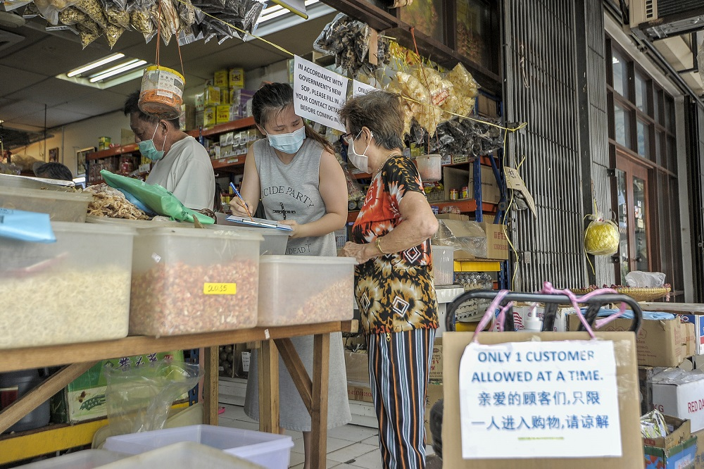 A worker at a Chinese sundry shop collects customers' details as part of new standard operating procedures during the conditional movement control in Kuala Lumpur. Experts have argued that face masks are crucial to contain the Covid-19 outbreak, pointing to data suggesting a high number of infections are caused by asymptomatic cases. ― Picture by Shafwan Zaidon