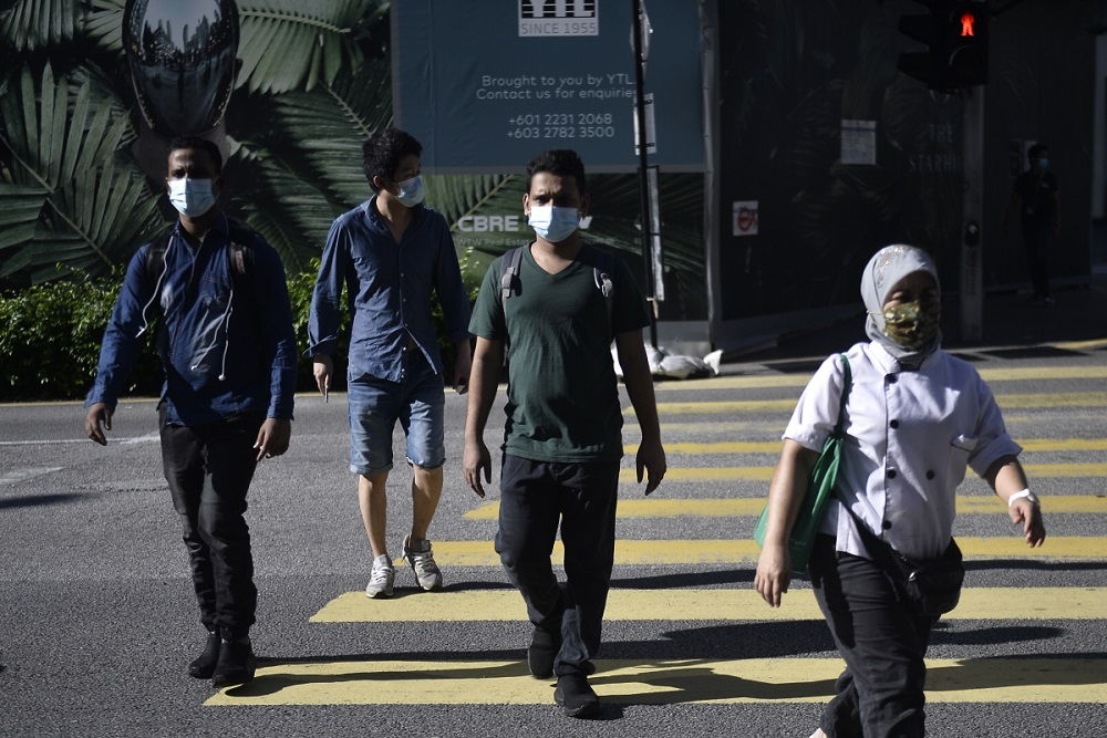 Pedestrians are seen walking on the streets of Kuala Lumpur on first day of CMCO, May 4, 2020. ― Picture by Miera Zulyana