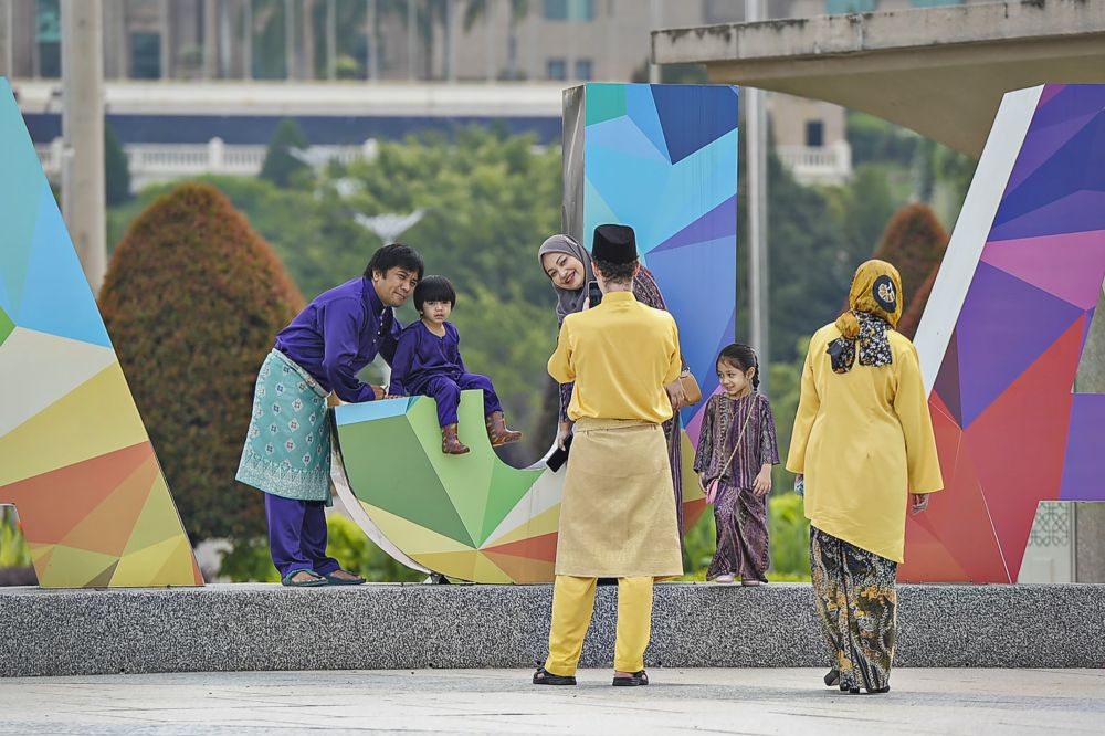 Members of the public pose for pictures at Dataran Putrajaya on the first day of Syawal in Putrajaya, May 24, 2020. — Picture by Shafwan Zaidon
