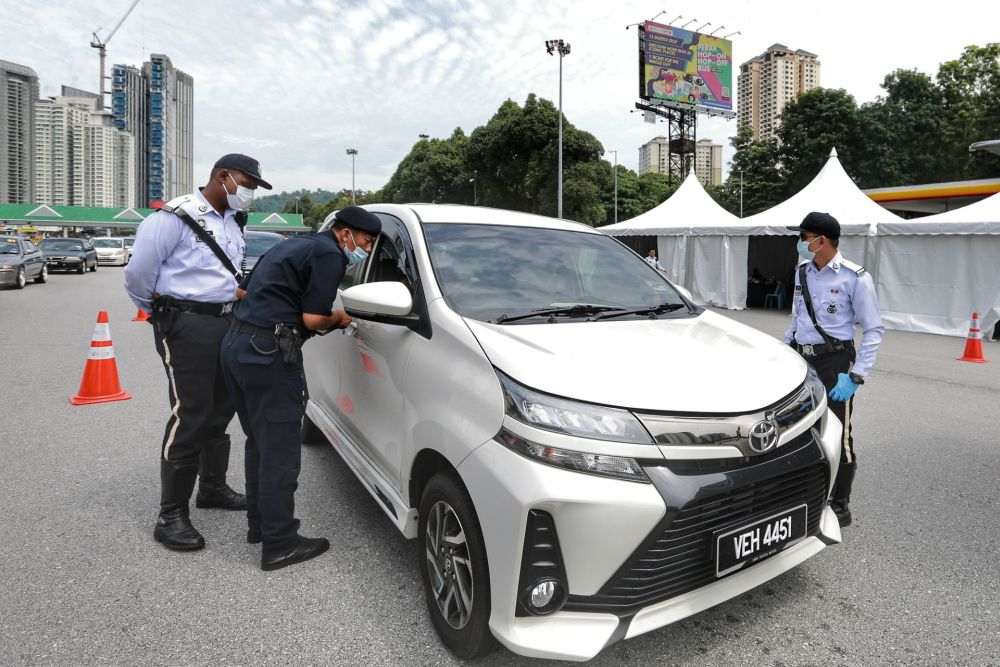 Police personnel conduct checks on vehicles at the Duta toll exit in Kuala Lumpur May 27, 2020. — Picture by Ahmad Zamzahuri