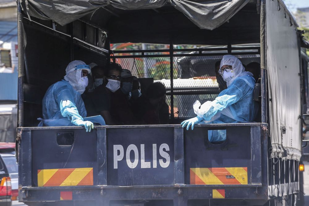 Undocumented migrants are pictured aboard a police truck following raids by the Immigration Department in Selayang Baru, Kuala Lumpur May 14, 2020. — Picture by Hari Anggara