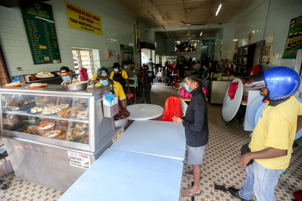 Members of the public observe social distancing guidelines while waiting to pack food at Nasi Kandar Ayam Merah in Ipoh May 4, 2020. — Picture by Farhan Najib
