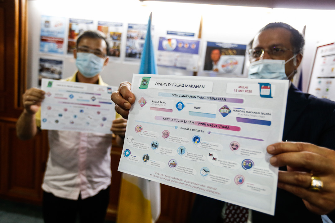 Penang exco Jagdeep Singh Deo (right) and mayor Datuk Yew Tung Seang hold up a copy of the new SOP for restaurant operators during a press conference at Komtar, George Town May 13, 2020. — Picture by Sayuti Zainudin