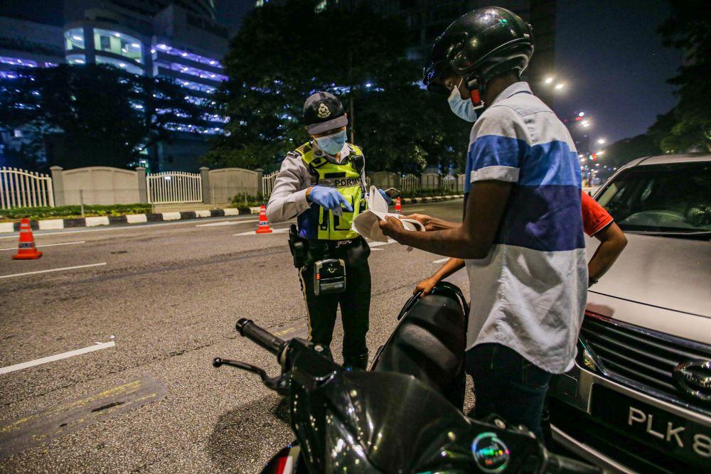 Traffic police personnel conduct checks on motorists during a roadblock on Jalan Raja Laut in Kuala Lumpur May 30, 2020. — Picture by Hari Anggara