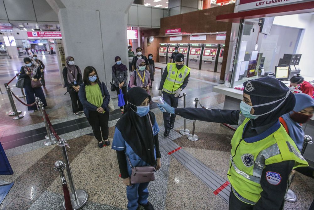 Commuters have their temperature checked at the KL Sentral LRT station on the first day of the conditional movement control order in Kuala Lumpur May 4, 2020. Transport Minister Datuk Seri Wee Ka Siong today said Covid -19 preventive measures including cleaning and disinfection exercise would also be conducted. — Picture by Hari Anggara