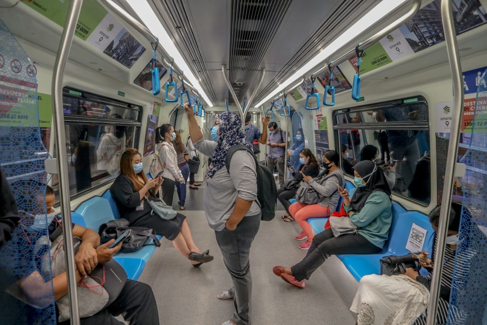 Commuters are pictured aboard an MRT train in Kuala Lumpur. — Picture by Firdaus Latif