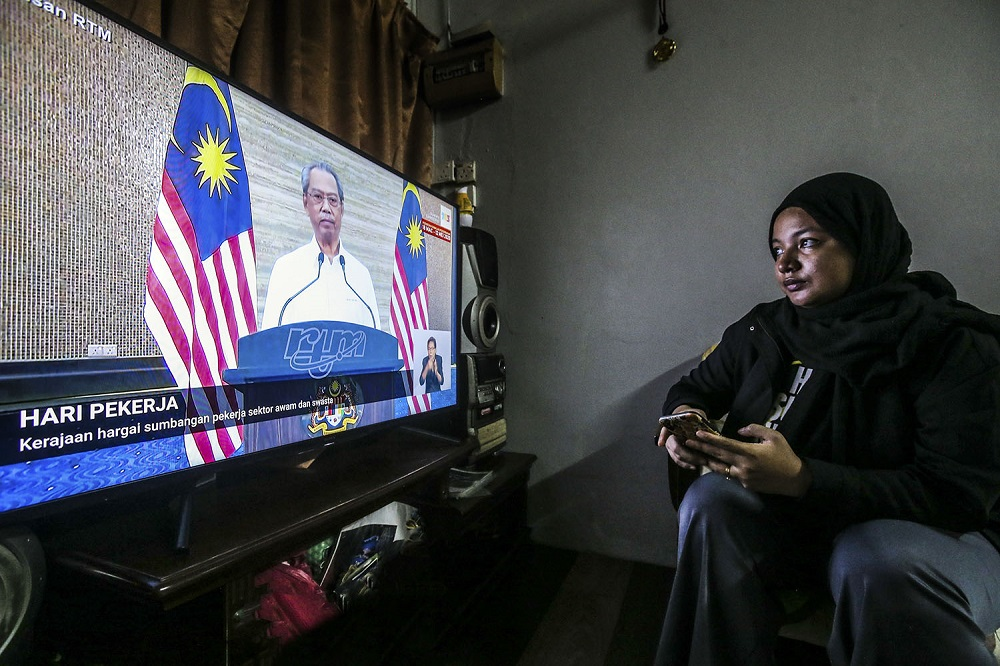 A woman watches the live telecast of Prime Minister Tan Sri Muhyiddin Yassin speaking about the fourth phase of the MCO in Kuala Lumpur May 1, 2020. ― Picture by Hari Anggara