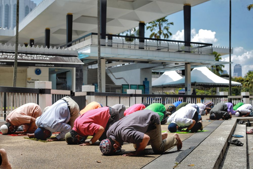 Muslims perform Friday prayers outside the National Mosque in Kuala Lumpur May 15, 2020. — Picture by Ahmad Zamzahuri