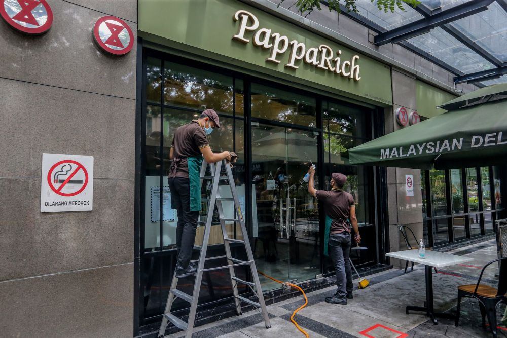 PappaRich staff carry out sanitising and cleaning work within the premises in Kuala Lumpur as eateries gets ready to resume dine-in services starting tomorrow. — Picture by Firdaus Latif