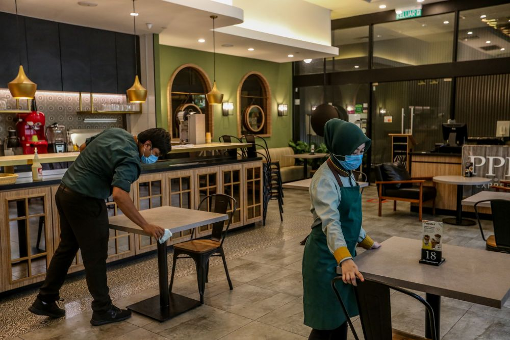 PappaRich staff carry out sanitising and cleaning work within the premises in Kuala Lumpur as eateries get ready to resume dine-in services in May. — Picture by Firdaus Latif