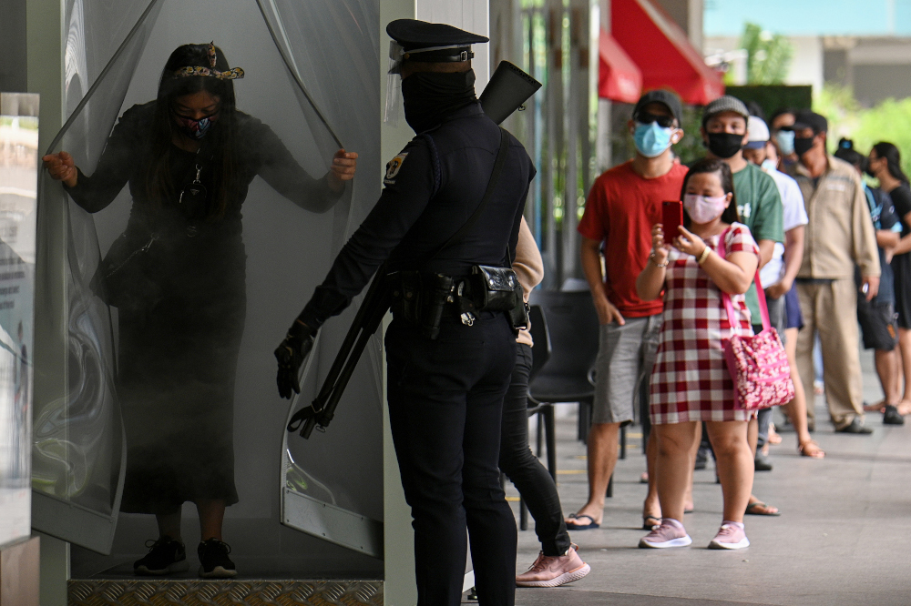 A security guard watches as a shopper exits from a disinfection channel installed at the entrance of a shopping mall as a preventive measure against the Covid-19 coronavirus, in Manila May 16, 2020. — AFP pic