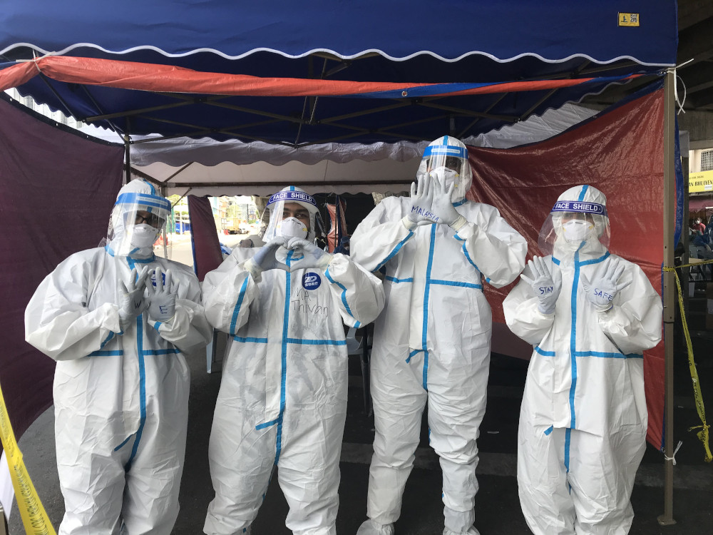Several health workers get ready at the Covid-19 screening area at the Pudu Market in Kuala Lumpur May 5, 2020. — Picture by Radzi Razak