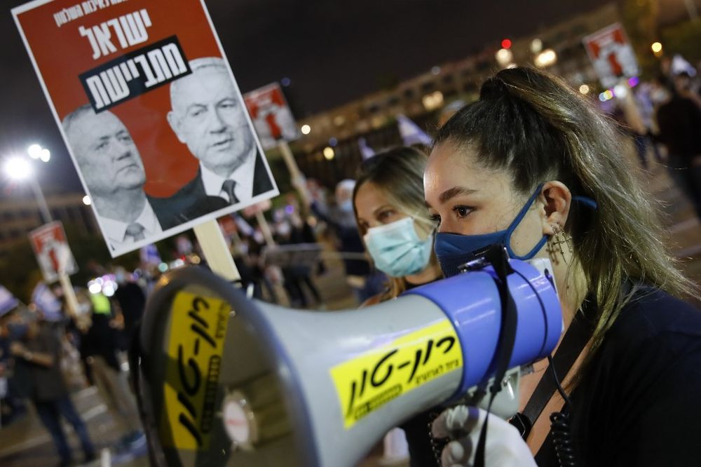 """An Israeli protester, wearing a protective mask and standing with others distanced two metres apart from each other due to the Covid-19 coronavirus pandemic, stands with a megaphone while another holds a sign showing the faces of Israeli Prime Minister Benjamin Netanyahu (right) and ex-rival Benny Gantz with a caption in Hebrew reading """"Israeli ashamed"""" attends a demonstration in Rabin Square in the Israeli coastal city of Tel Aviv on May 9, 2020, calling for """"a quality government"""" before the formation of a new government later in the week amid negotiations between the two politicians. — AFP pic"""