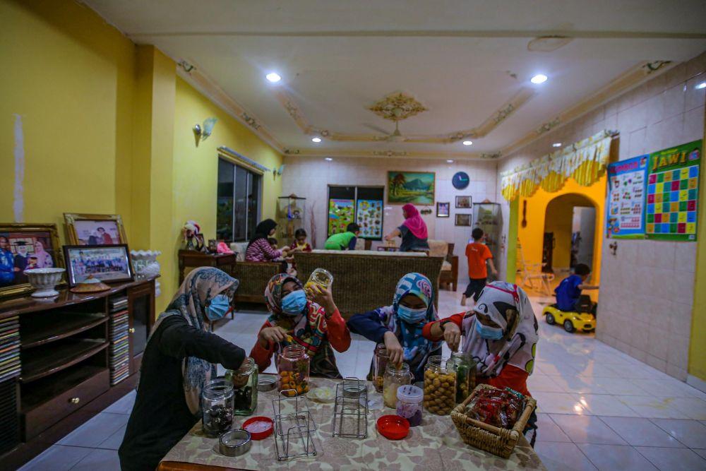 Family members prepare jars of cookies at home in Kampung Changkat, Gombak on the eve of Hari Raya Aidilfitri May 23, 2020. — Picture by Hari Anggara