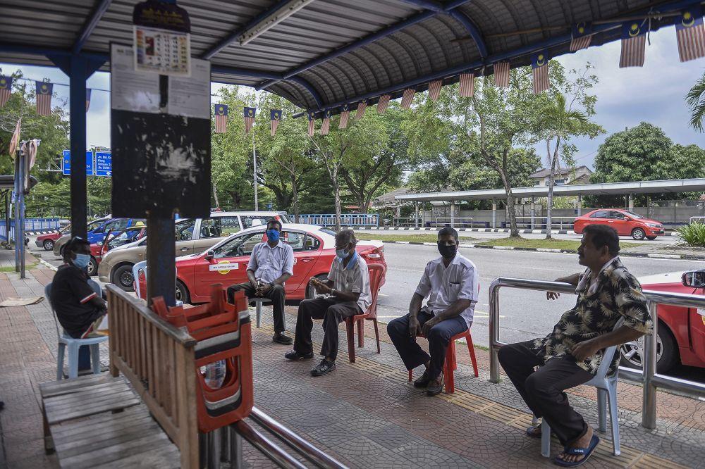 Taxi drivers wait for passengers at a taxi station in Shah Alam during the conditional movement control order May 6, 2020. — Picture by Miera Zulyana